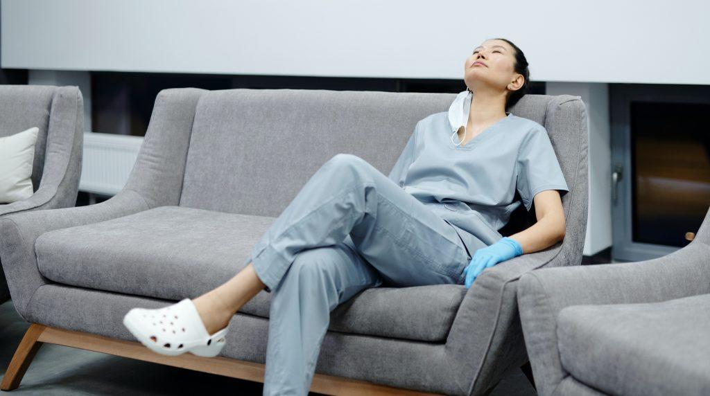 vård- och omsorgsarbetare sitter i en soffa med avtaget munskydd och plasthandskar och blundar